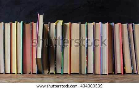 Books in the colored covers on the shelf in the background of a school blackboard. #434303335