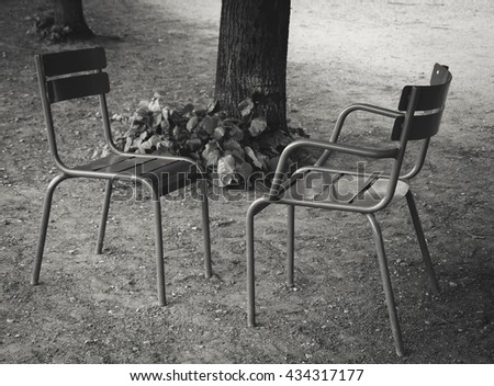 Dialogue. Two chairs facing each other in Tuileries garden. Paris (France) Black and white photo.