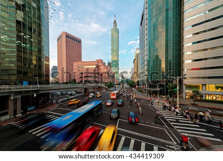 View of a busy street corner in Downtown Taipei City at rush hour with cars & buses dashing by, Taipei 101 Tower & World Trade Center Building in Xinyi Financial District & people passing on crosswalk #434419309