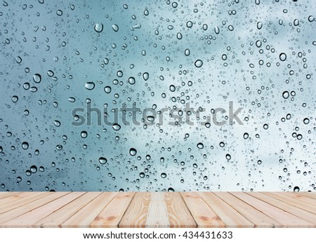 Wood table top on rain drops on clear window - can be used for display or montage your products #434431633