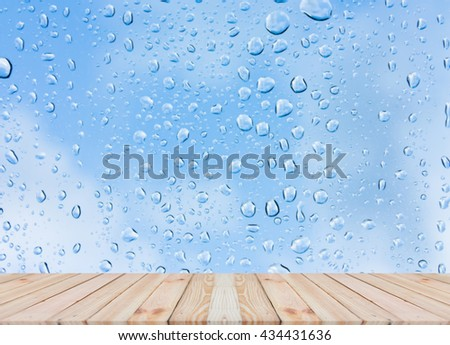 Wood table top on rain drops on clear window - can be used for display or montage your products #434431636