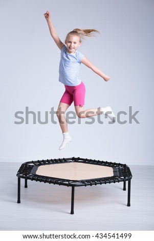 Happy school girl jumping on a small trampoline in a very bright room #434541499