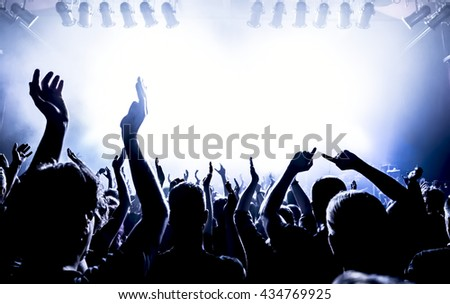 silhouettes of concert crowd in front of bright stage lights #434769925