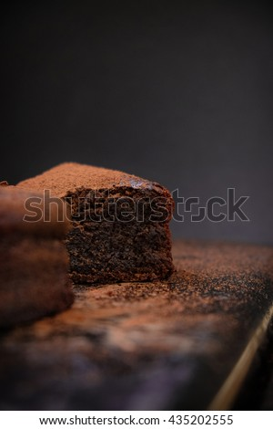A close up slice of flourless chocolate cake on a dark background. Dark food photography. Free text space layout.