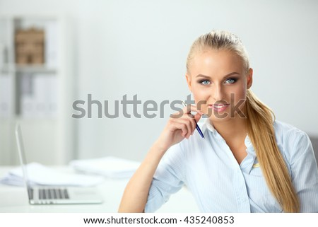 Attractive businesswoman sitting on a desk with laptop in the office #435240853