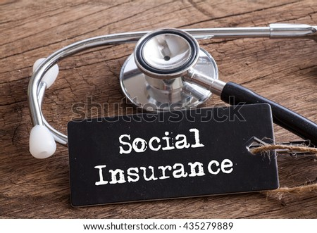 Social Insurance words written on label tag with Stethoscope on wood as medical concept #435279889