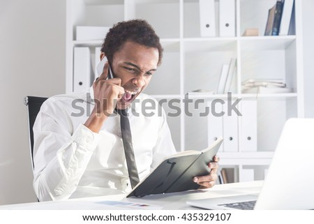 Furious african american businessman sitting at office desk with notepad in hand and shouting at interlocutor over the phone. Concept of stress and authority abuse #435329107