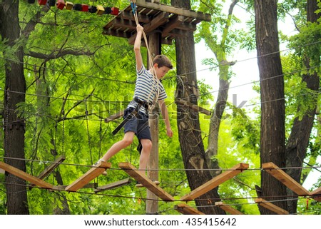 Boy is climbing in a rope park over the trees #435415642