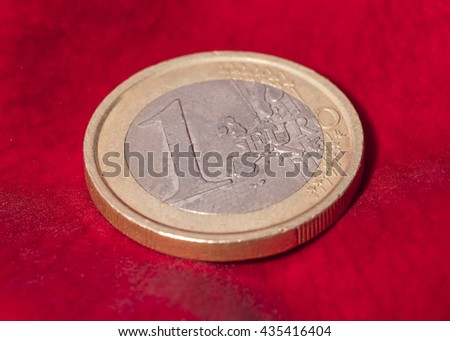 One euro coin on red rose petal #435416404
