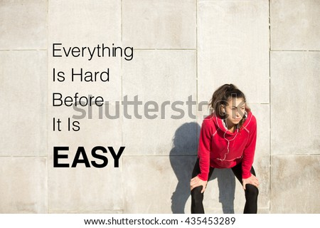 "Portrait of young beautiful female leaning on gray background while resting after everyday training. Motivational phrase ""Everything is hard before it is easy"""
