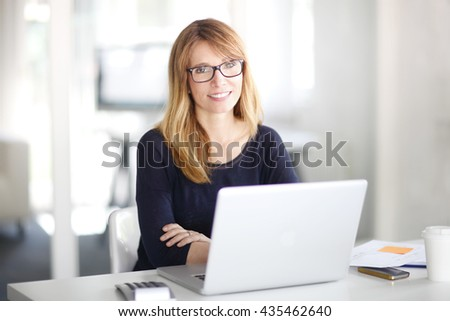 Portrait of an executive investment advisor professional woman sitting at office and working on laptop. #435462640