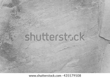 A rough piece of gray stone with a natural pattern-cracks. Texture of slate, granite, rough wall, untreated plaster #435579508