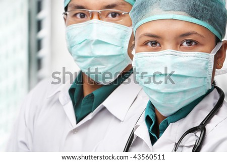 Two Asian surgeon posing to camera with protective gear #43560511