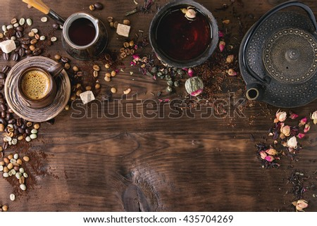 Food background tea and coffee theme. Different black and green dry tea, different coffee beans, cup of hot tea and coffee,  teapot over dark wooden background. Top view. Space for text #435704269
