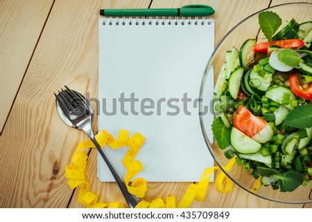 Diet plan, menu or program, tape measure and diet food of fresh salad on wood background, weight loss and detox concept, top view #435709849