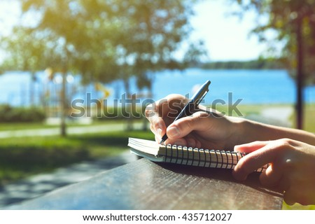 girls hands with pen writing on notebook in park #435712027