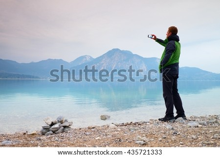 Tall man hold cellphone, take picture of autumn mountain lake scenery after rainy day. Vivid and vignetting effect. Poor lighting conditions.