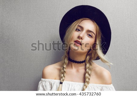 Pigtails. Close up of beautiful young blonde woman with black hat. Her hair is tied in two big ponytails. Around neck she has black choker. Professional make-up, hair style and styling.  #435732760