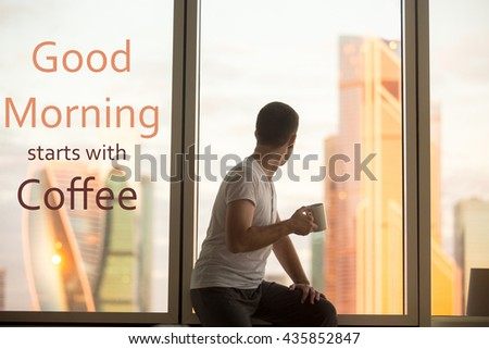 """Rear view of young man sitting on window with coffee cup looking at dawn city scenery. Motivational text """"Good morning starts with coffee"""""""