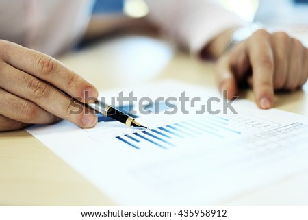 Business adviser analyzing financial figures denoting the progress in the work of the company #435958912