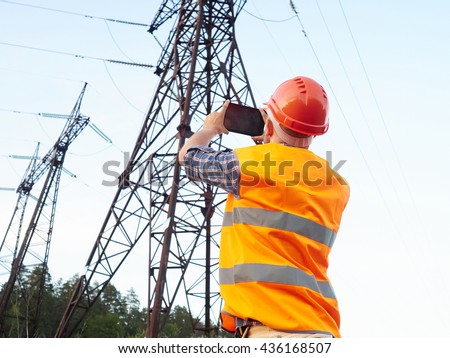 Electrical engineer working. Talking on the phone and working on the tablet.Checking the power grids.    #436168507
