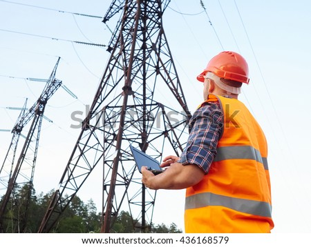Electrical engineer working. Talking on the phone and working working on a laptop.Checking the power grids.   #436168579
