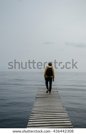 Pier on Lake Baikal, Russia. Male tourist in yellow jacket dramatically walks on the pier. loneliness concept. Hipster toning. Soft focus.  #436442308