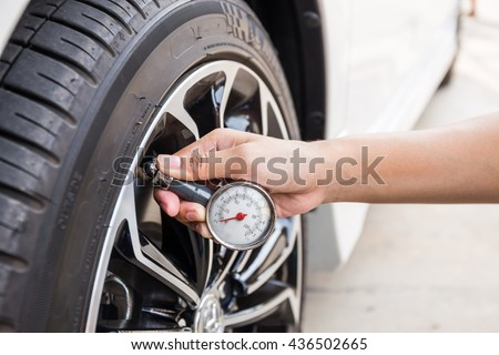 Close-Up Of Hand holding pressure gauge for car tyre pressure measurement #436502665