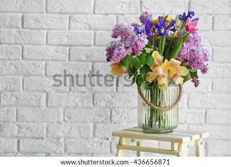 Bouquet of fresh spring flowers on brick wall background #436656871