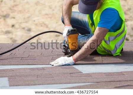 Roofer builder worker with nailgun installing Asphalt Shingles or Bitumen Tiles on a new house under construction #436727554