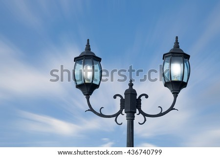 vintage  lighting pole with twin double lamp lantern on background of blue sky. #436740799