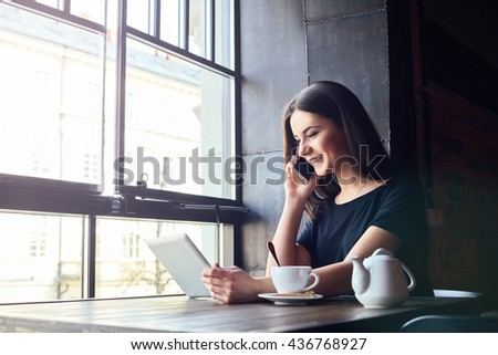Young attractive girl with cute smile talking on mobile phone while sitting alone in coffee shop during free time and working on tablet computer. Happy female having rest in cafe. Lifestyle #436768927