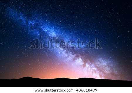 Night landscape with colorful Milky Way and yellow light at mountains. Starry sky with hills at summer. Beautiful Universe. Space background Royalty-Free Stock Photo #436818499