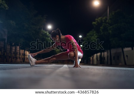 Young girl doing fitness outdoors at night. #436857826