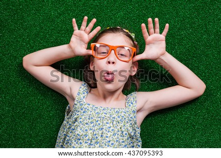 Happy little girl is lying on artificial grass and making face. #437095393