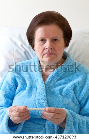 Sick senior woman with thermometer. #437129893
