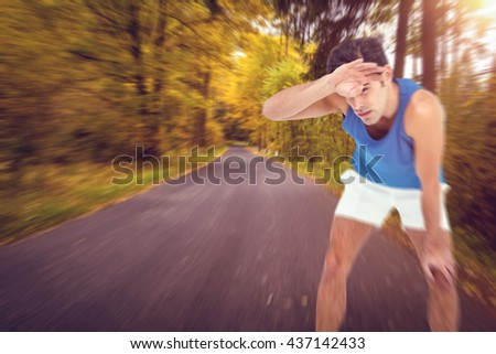 Tired athlete wiping his sweat with hand against country road along trees in the lush forest #437142433