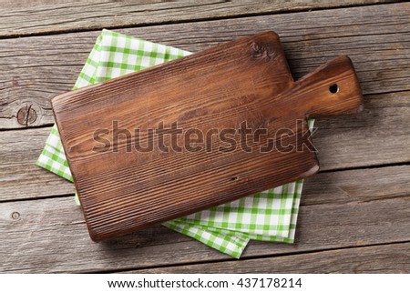 Cutting board over towel on wooden kitchen table. Top view Royalty-Free Stock Photo #437178214
