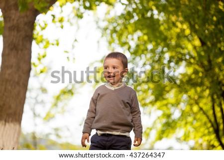 Cute happy baby boy walking in summer park . Outdoor portrait #437264347