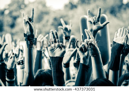 Hand fans during a concert. Sign of the horns. Open air festival Royalty-Free Stock Photo #437373031