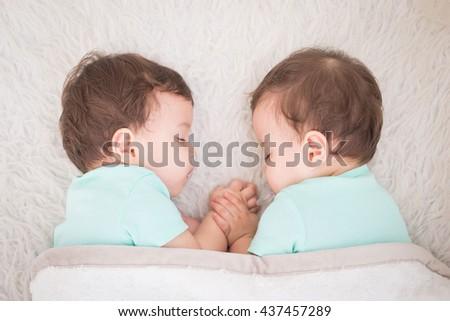 Newborn beautiful baby twins sleeping with pacifier. Closeup portrait, caucasian child