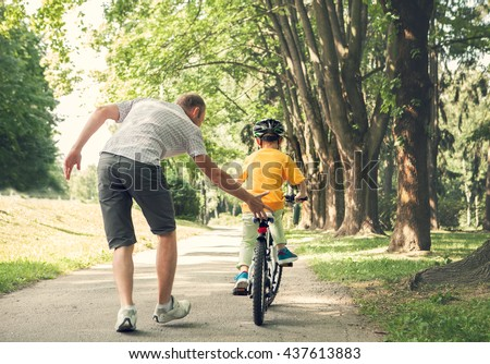 Father learn his little son to ride a bicycle #437613883