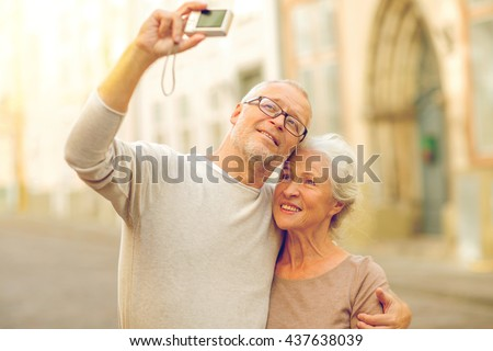 age, tourism, travel, technology and people concept - senior couple with camera taking selfie on street #437638039