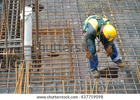 MALACCA, MALAYSIA -MAY 27, 2016: Construction workers fabricating steel reinforcement bar at the construction site in Malacca, Malaysia. The reinforcement bar was ties together using tiny wire.   #437759098