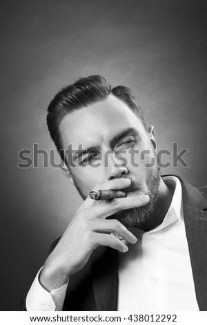 Young handsome bearded caucasian man smoking a cigar. Perfect skin and hairstyle. Wearing grey suit and white shirt. Studio portrait on gradient black to grey background. Black and white #438012292
