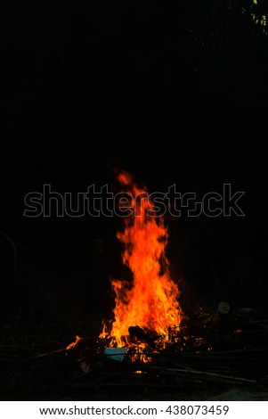 Flames in a bonfire on black background #438073459