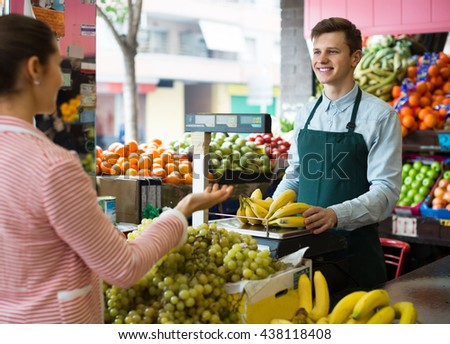 adult  seller weighing bananas on scale for young woman #438118408