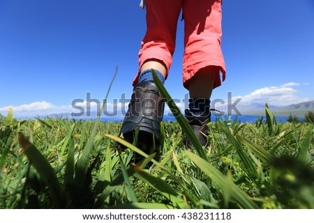hiker legs on a grass mountain top with first person perspective view  #438231118