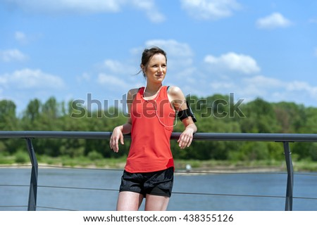 Fit woman jogger resting after run listening music. #438355126