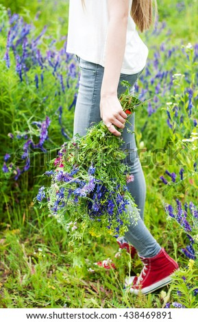girl holding a bouquet of wildflowers - arms and legs close-up #438469891
